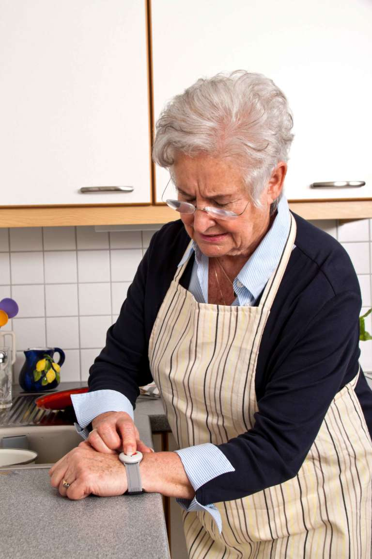 Fester Hausnotruf. Seniorin mit Notrufarmband zu Hause.