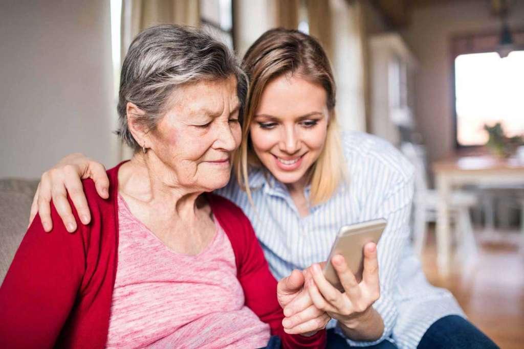 Seniorin und Enkelin schauen sich auf dem Handy den Hausnotruf an.