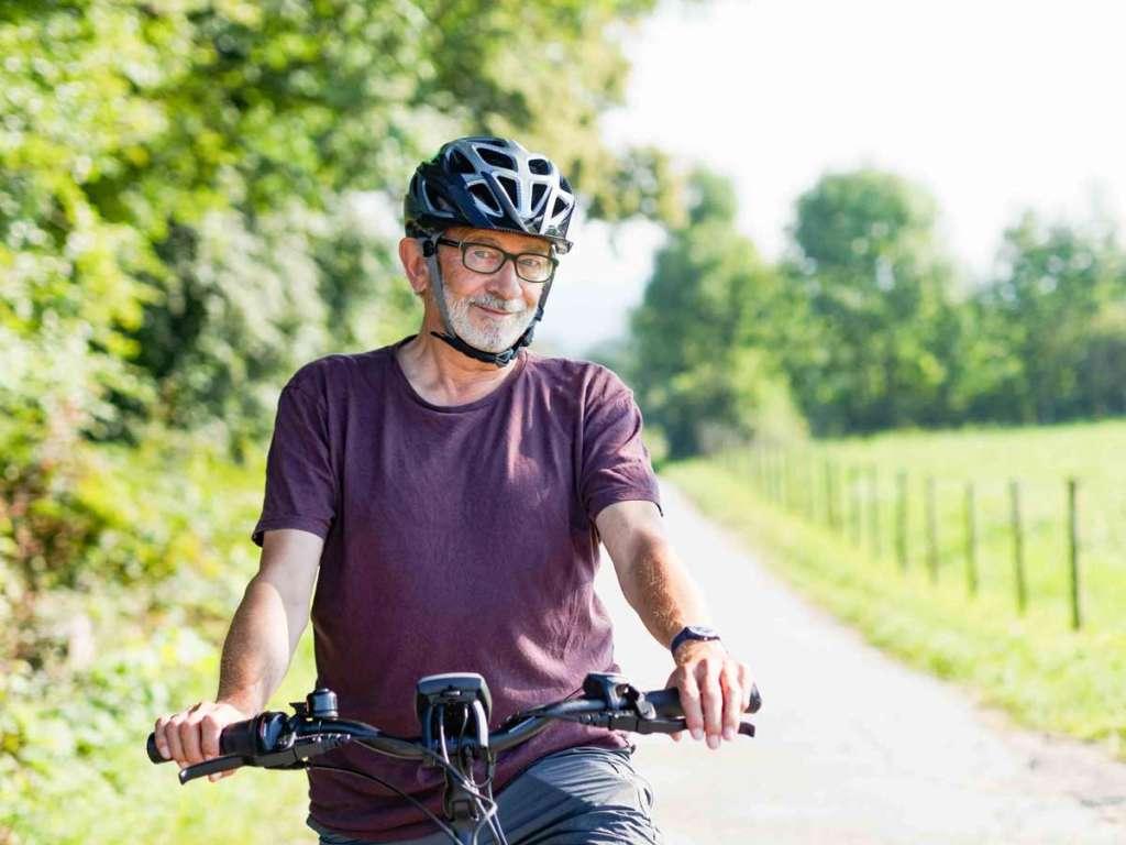 Älterer Mann macht Radtour mit E-Bike und trägt Notrufarmband für den mobilen Notruf